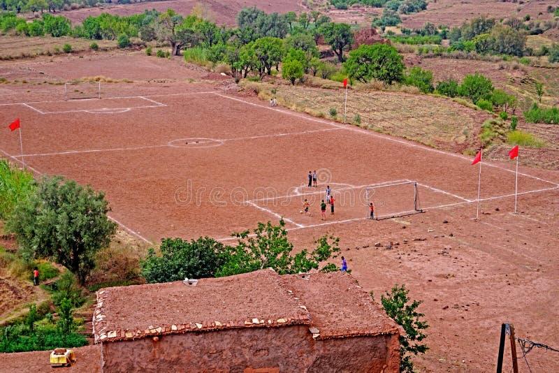 与踢在阿特拉斯山脉的孩子的一个足球场橄榄球在摩洛哥 免版税库存照片