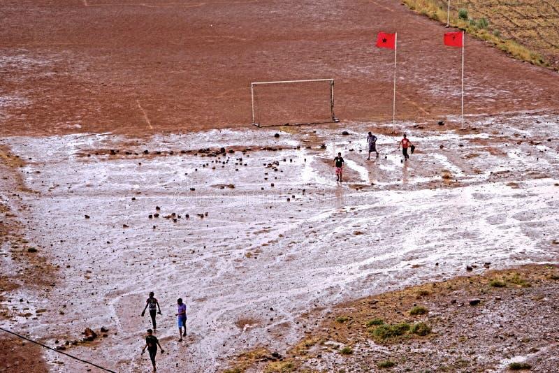 与踢橄榄球的孩子的一个足球场在阿特拉斯山脉的雨以后在摩洛哥 免版税库存照片