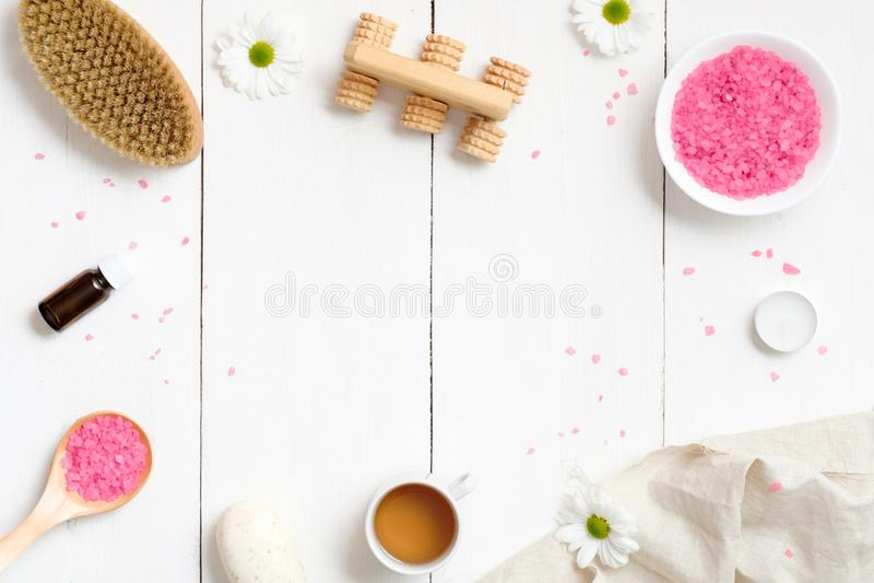与身体刷子,桃红色腌制槽用食盐,毛巾,有机彗星肥皂,在木背景,顶视图,地方的精油的温泉设置为 免版税库存照片