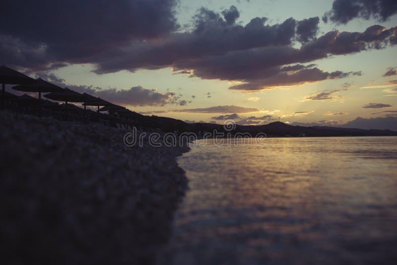 与躺椅和伞的海海滩在日落以后 在多云天空的晚上海滩 在热带海滩的暑假 免版税库存照片
