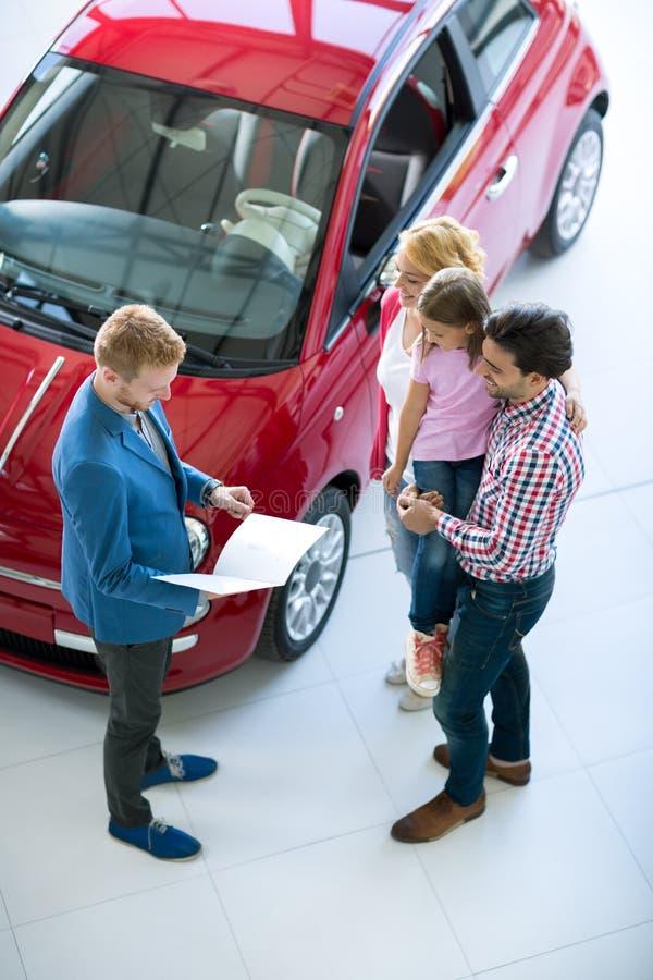 与车商的家庭在售车行交谊厅 免版税库存图片