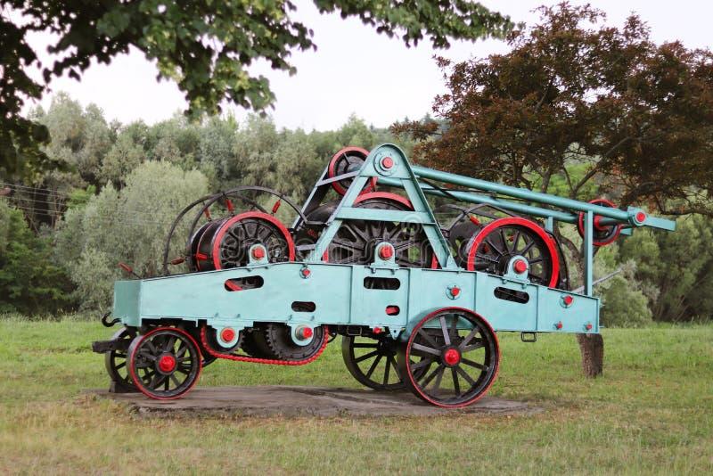 与轮子、飞轮和链子的电源装置 收获处理的农业机制 重的工程学 金属化建筑 免版税库存照片