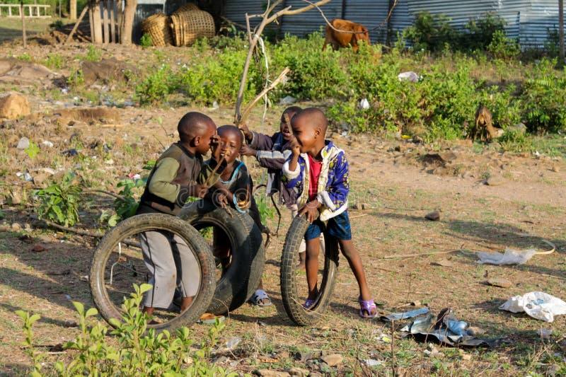 与轮子的非洲贫穷的男孩戏剧 免版税图库摄影
