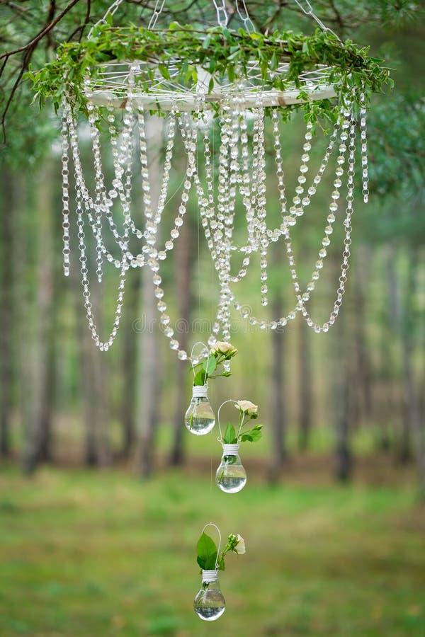 与轮子,玻璃珠和玫瑰的婚礼装饰在电灯泡 图库摄影