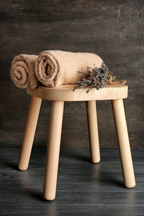与软的毛巾和干淡紫色的板凳在黑暗的背景 库存图片