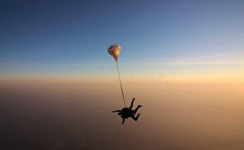 与软的焦点的Skydiving纵排日落在背景 图库摄影