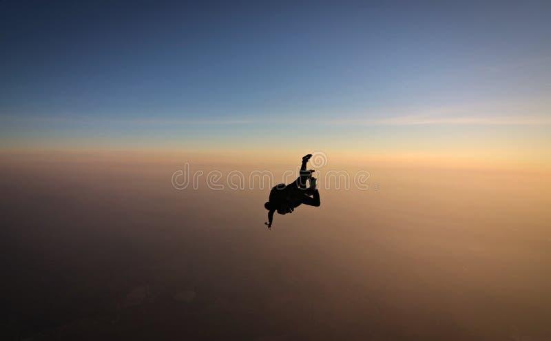 与软的焦点的Skydiving纵排日落在背景 免版税库存照片