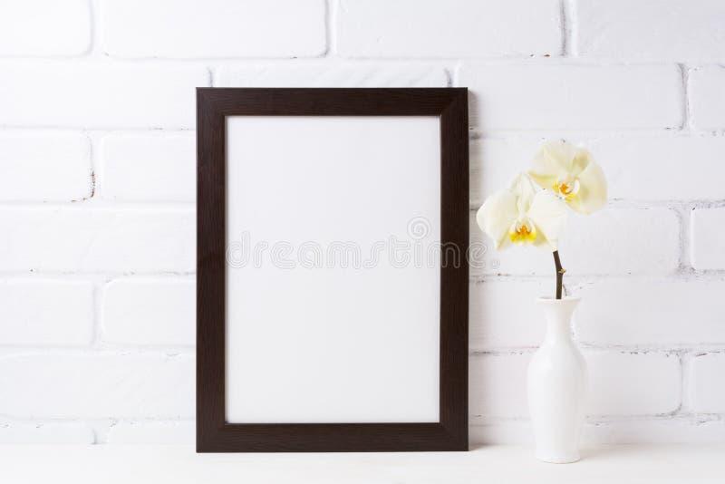 与软的黄色兰花的黑棕色框架大模型在花瓶 免版税库存图片
