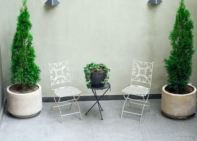 与轻的大理石地板、植物和白色庭院家具的美丽的现代大阳台 库存图片