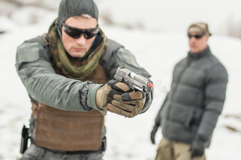与辅导员的军队战士训练作战枪冬天雪射击 免版税库存照片