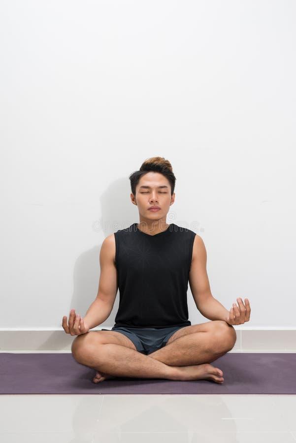 与辅导员的年轻黑人实践的瑜伽教训,坐在Sukhasana锻炼 免版税库存照片