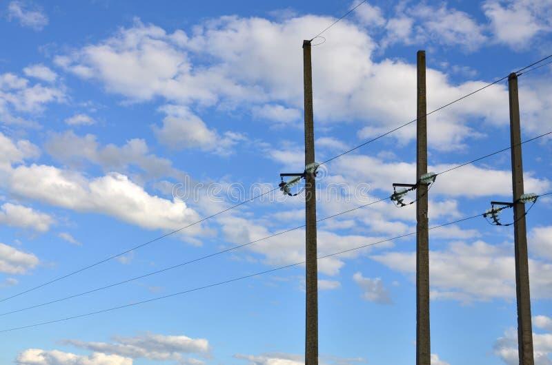 与输电线导线的具体杆以蓝色多云sk为背景的 图库摄影