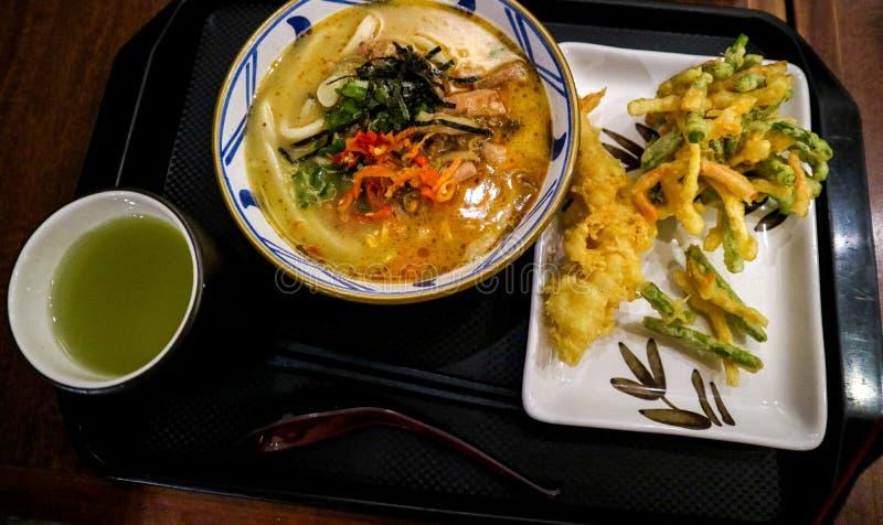 与辛辣料理的日本风格面条加上温暖的饮料 免版税图库摄影