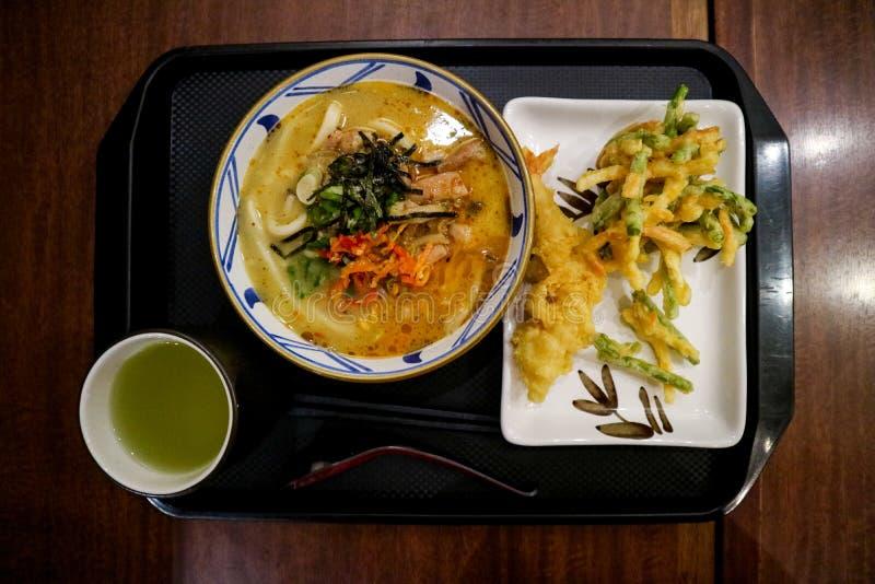 与辛辣料理的日本风格面条加上温暖的饮料 库存照片