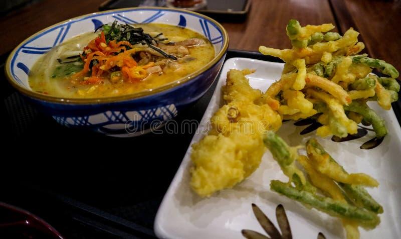 与辛辣料理的日本风格面条加上温暖的饮料 免版税库存图片