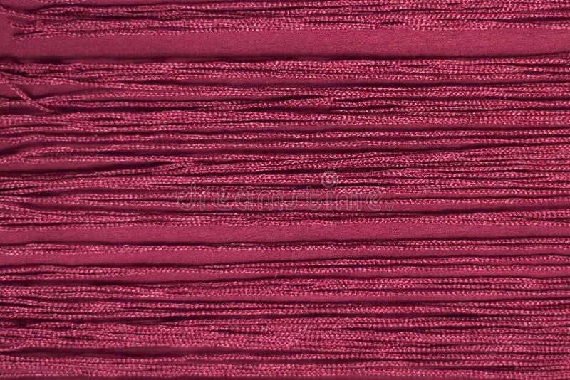 与边缘的褐红的织品 特写镜头 背景 免版税图库摄影