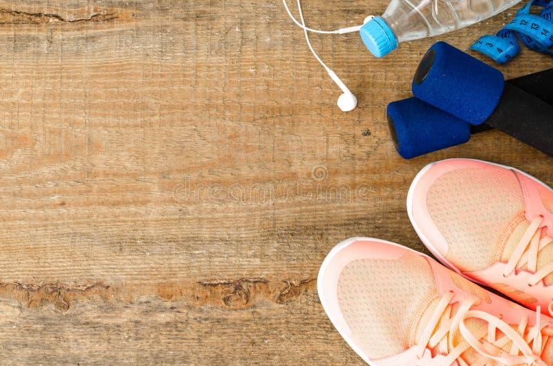 与运动鞋、哑铃、水瓶和耳机的健身概念在木背景 免版税库存照片
