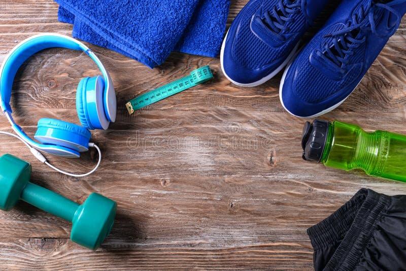 与运动鞋、耳机、哑铃和瓶的平的被放置的构成在木背景的水 健身房锻炼 图库摄影