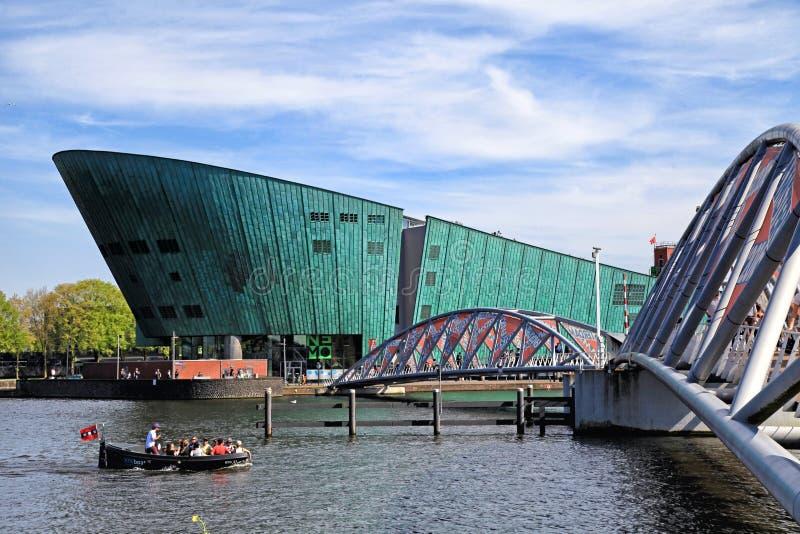 与运河、游人和科学中心NEMO的都市风景在阿姆斯特 免版税库存照片