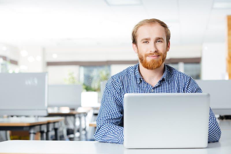 与运转在工作场所的膝上型计算机的愉快的商人在办公室 免版税库存图片