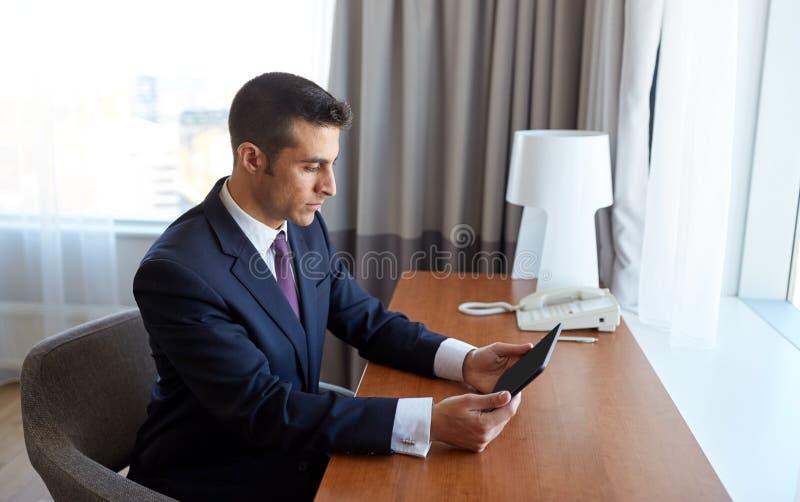 与运转在旅馆客房的片剂个人计算机的商人 免版税库存图片
