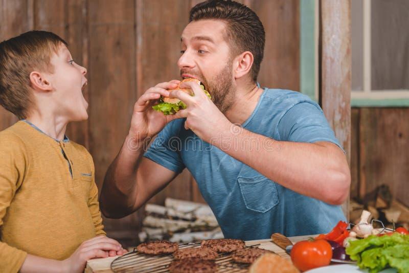 与近小儿子的食人的自创汉堡 免版税库存图片