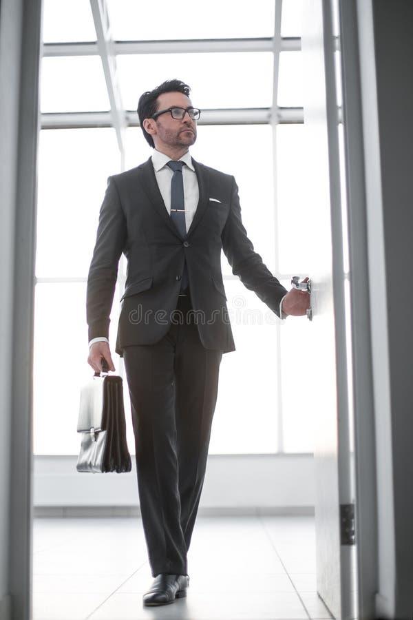 与进入他的客户` s办公室的一个皮革公文包的商人 免版税库存图片