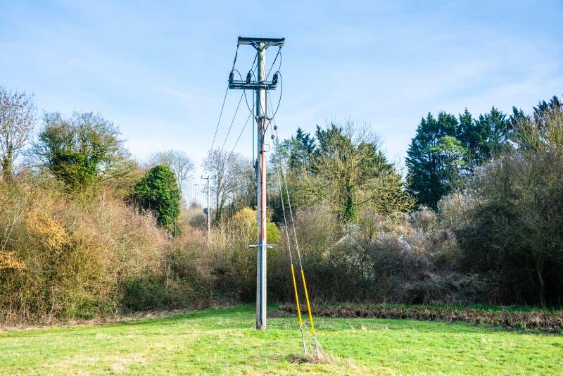 与进入地面和线的输电线的一根木输电线杆对其他杆 库存图片