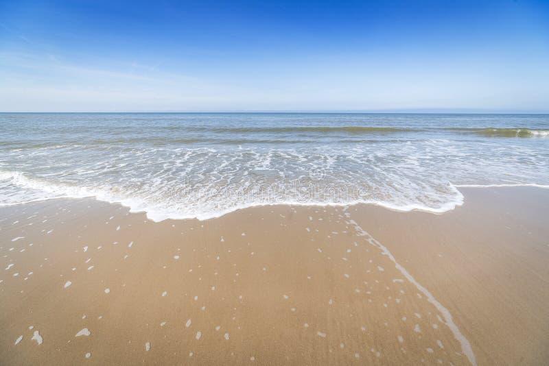 与进来在岸的小波浪的海滩 库存照片