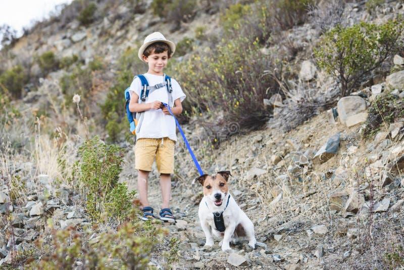 与远足由在塞浦路斯山的狗友好的足迹的宠物的孩子 免版税库存照片