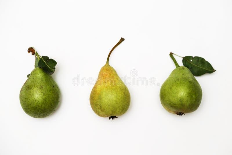 与连续说谎在白色背景的小树枝的三个成熟绿色梨 顶视图 库存图片