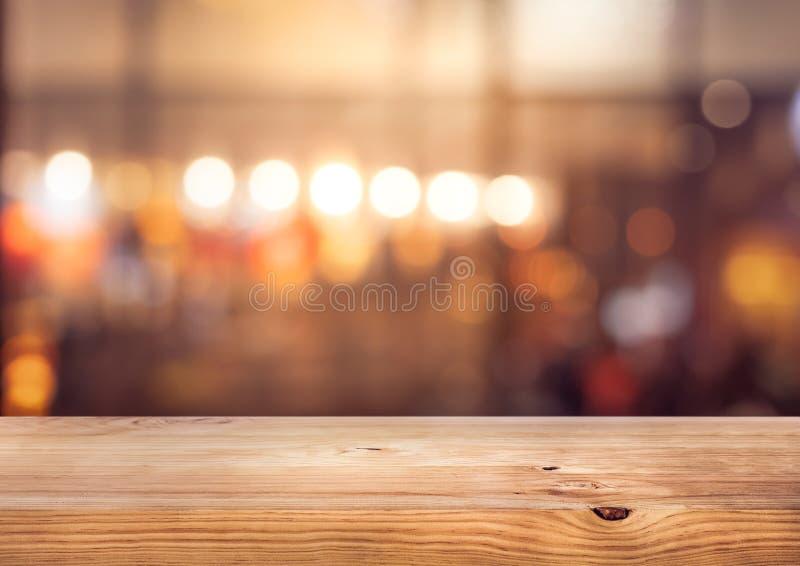 与迷离五颜六色的轻的bokeh的木台式酒吧在咖啡馆,餐馆背景 免版税库存照片