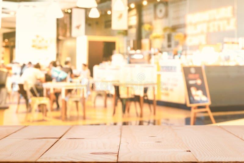 与迷离咖啡店的木桌面或咖啡馆餐馆和促进签字,抽象bokeh光图象背景 库存图片