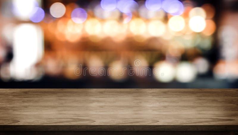 与迷离夜总会酒吧柜台的木台式与bokeh光 免版税库存照片