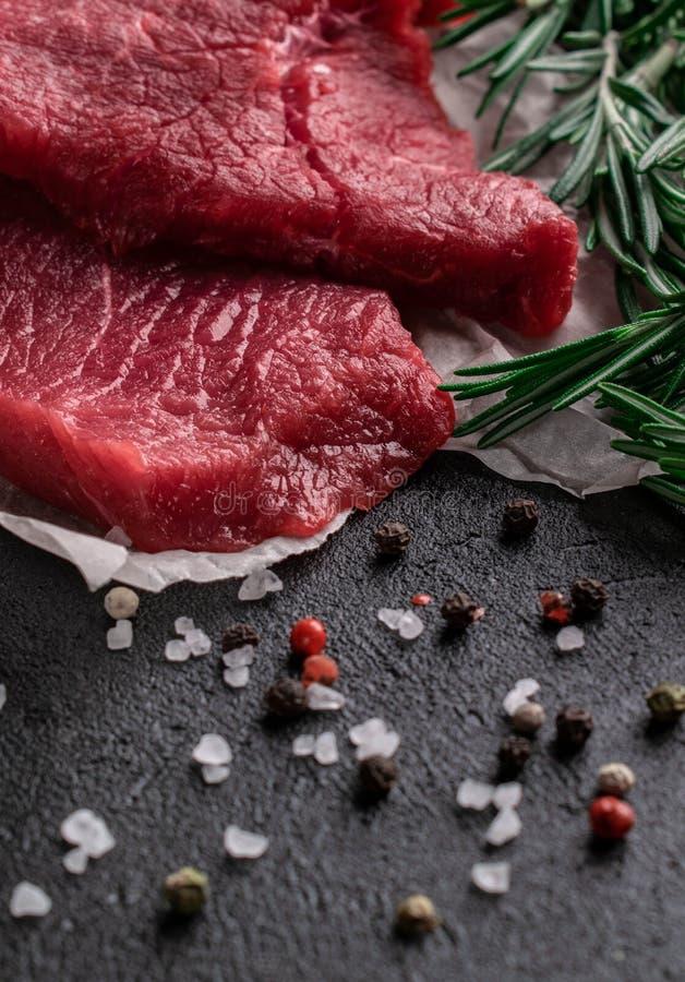与迷迭香分支的未加工的牛排在羊皮纸用胡椒和盐 库存照片