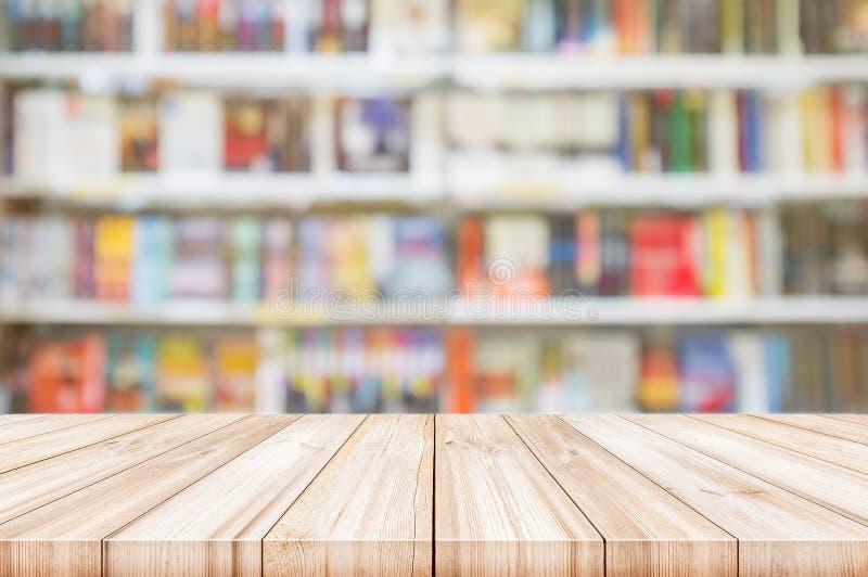 与迷离书架的空的木台式在书店backgr 免版税库存图片