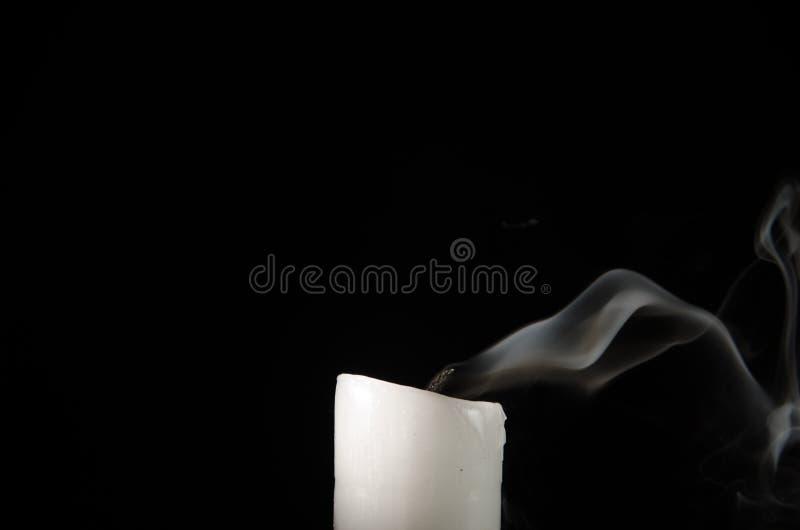 与退色的火焰的灼烧的在黑背景的蜡烛和烟 库存图片