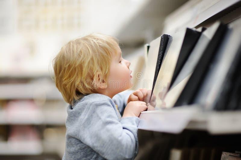 与选择他们的公寓的小男孩的家庭正确的家具在一家现代家庭家具店 免版税图库摄影