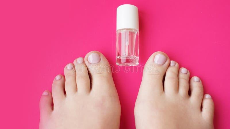 与透明指甲油的修脚在桃红色背景 免版税库存图片