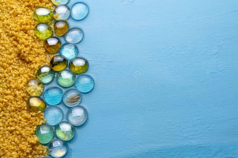 与透明石头的粗糙的沙子在蓝色清楚的水背景  E 海滩的模仿 免版税图库摄影