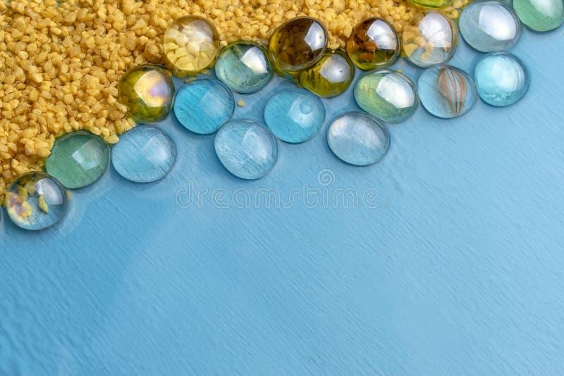 与透明石头的粗糙的沙子在蓝色清楚的水背景  E 海滩的模仿 免版税库存照片