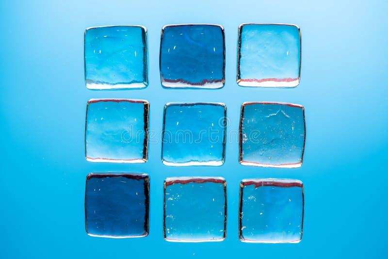 与透明象冰的立方体的时髦的蓝色背景饮料的 舱内甲板被放置的宏观照片 库存图片