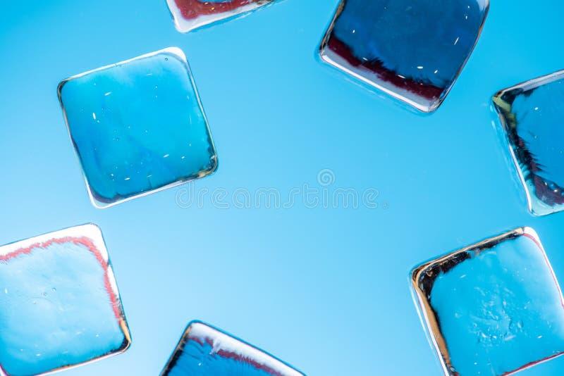 与透明象冰的立方体的时髦的蓝色背景饮料的 舱内甲板被放置的宏观照片 免版税图库摄影
