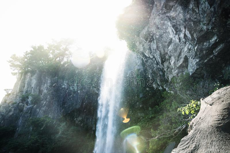 与透镜火光的Joengbang瀑布从阳光在西归浦,济州海岛,韩国 免版税库存图片