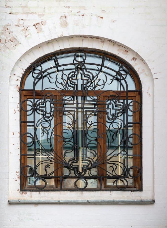 与透雕细工wrought-iron格子的美丽的装饰污迹玻璃窗在石墙 免版税库存照片