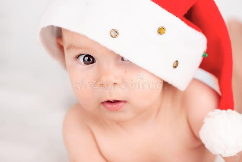与逗人喜爱的女婴的Xmas卡片有在米黄通风briht背景的圣诞老人帽子的与拷贝空间 库存照片