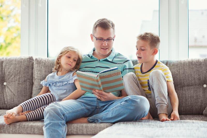 与逗人喜爱的孩子的年轻愉快的父亲阅读书在家 图库摄影
