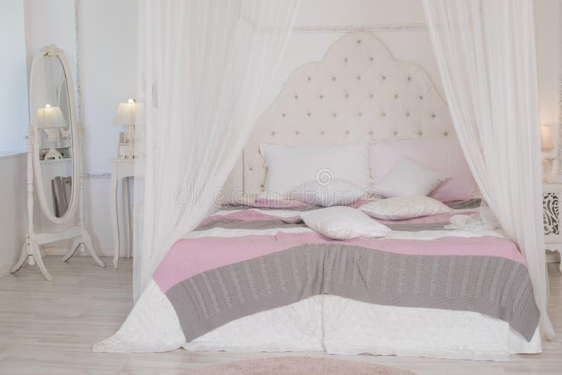与逗人喜爱的淡色卧具的大床在妇女` s室 淡色的现代卧室 有四根帐杆的卧床床 斯堪的纳维亚语 免版税图库摄影