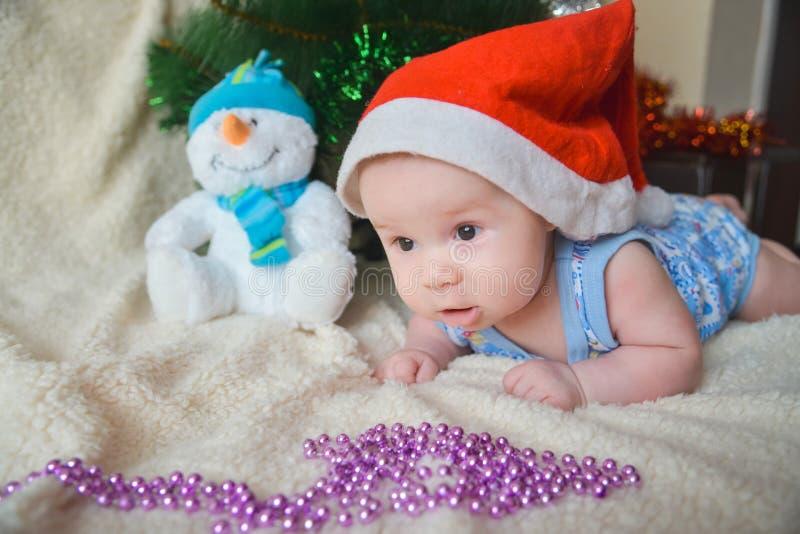 与逗人喜爱的男婴的圣诞卡在圣诞老人红色帽子weared 免版税图库摄影