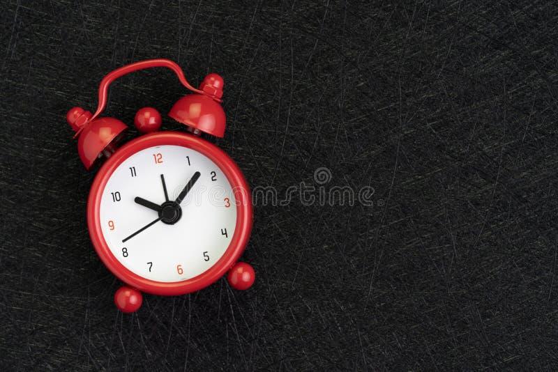 与逗人喜爱的红色闹钟的自我训练、时间、最后期限和会议日程背景在与纹理的深黑色背景 免版税库存照片